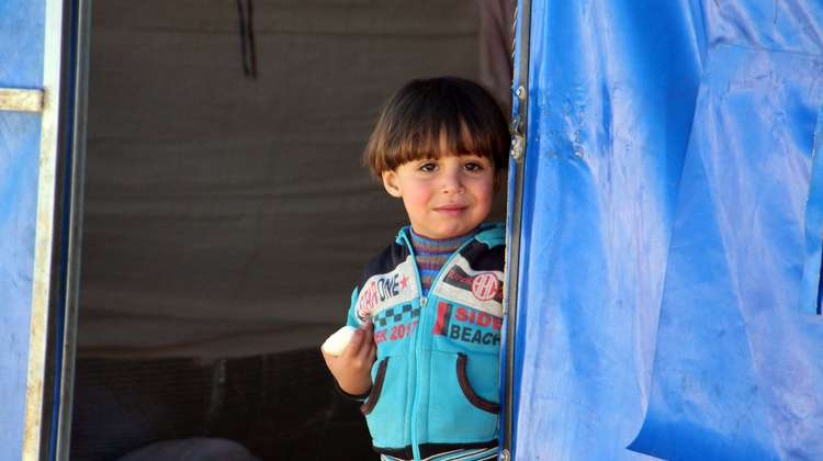 A child standing in the entrance of a tent, looking at the camera