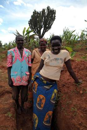 Mélanie Bacanurwanko (centre) with her husband and their daughter. Their field is steeply sloped and rocky; torrential rain has already eroded a lot of good soil.