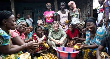 Welthungerhilfe President Marlehn Thieme opening cocoa fruits with a group of women in Sierra Leone.