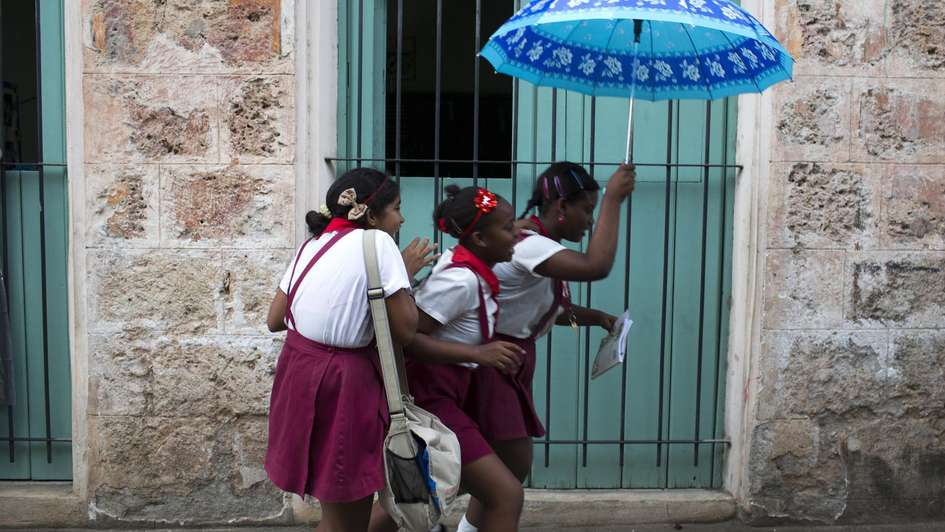 Girls in Cuba on their way to school in the rain.