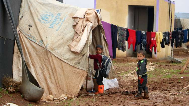 Two boys standing in front of a tent in a refugee camp in Idlib.