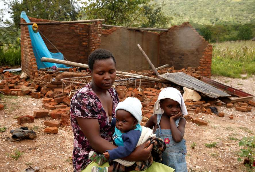 A woman and her children sitting in front of a house destroyed by cyclone Idai