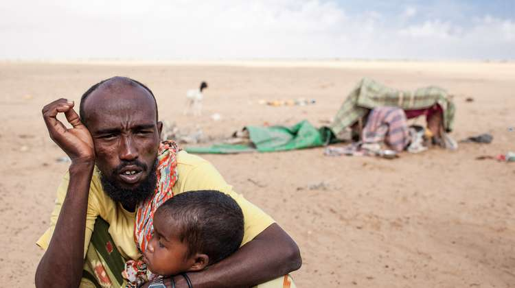 An exhausted father with his child during a drought in Somaliland