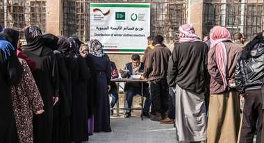 Refugees queuing at distribution of clothing vouchers in Idlib (Syria)