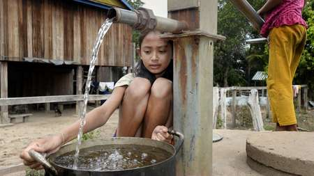 Girl fetching water at water well.