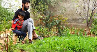 Obeida Yousef with his son in their vegetable garden