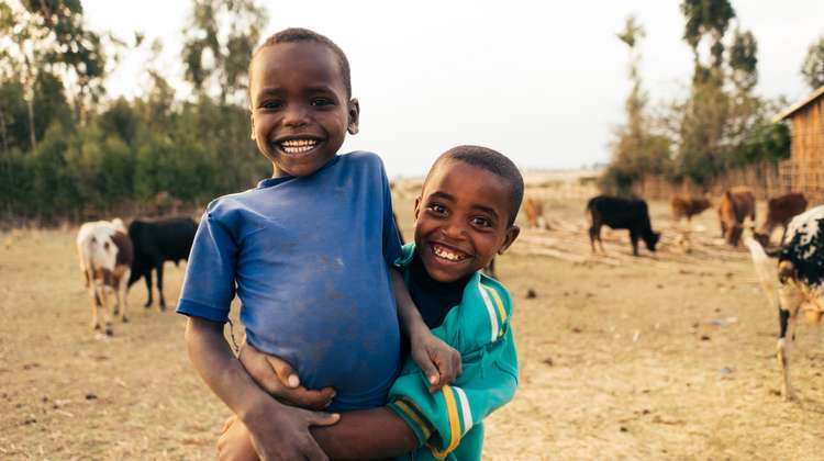 Two smiling boy standing on the field. In the back, you see some cows and a hut.