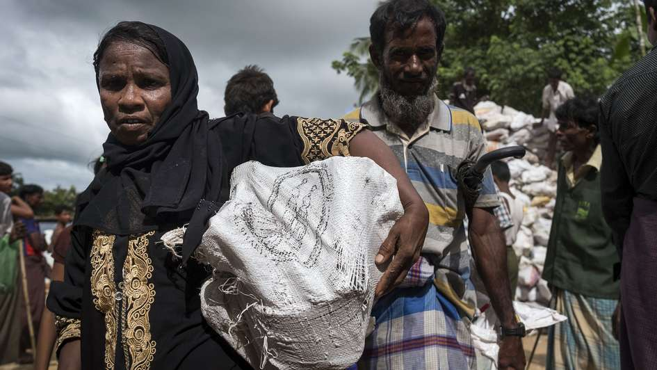 A woman in Hakimpara refugee camp, Bangladesh, with a sack full of fuel.