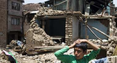 A boy in the front. Behind him a destroyed house.