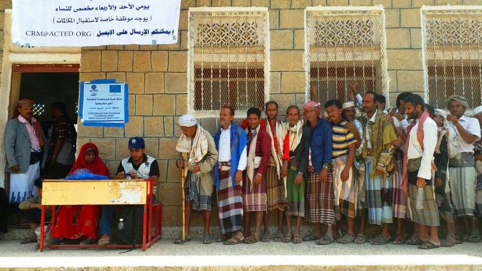 Beneficiaries lining up at a cash distribution in Yemen