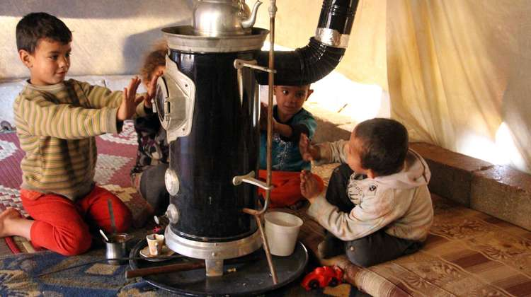 Four children sitting in front of a stove with their hands stretched out