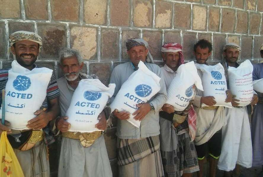 Men holding sacks full of seeds labelled 'ACTED'