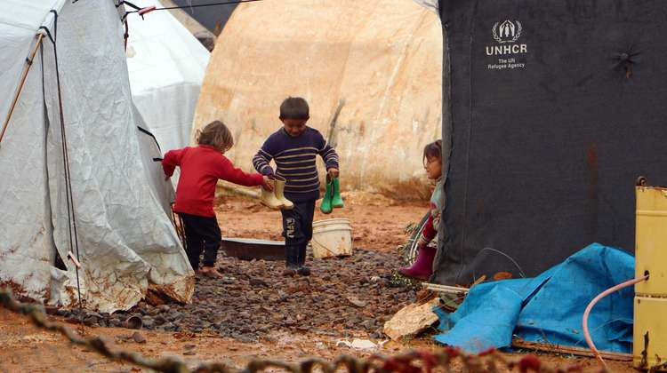 Three children holding rubber boots amongst tents in a refugee camp.