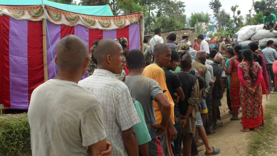 Men with shaved heads are standing in line