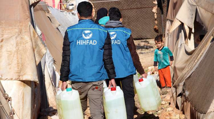 HIHFAD staff in blue jackets carry jerrycans with diesel as a boy watches on.