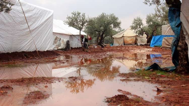 Mud and large puddles between tents in a refugee camp