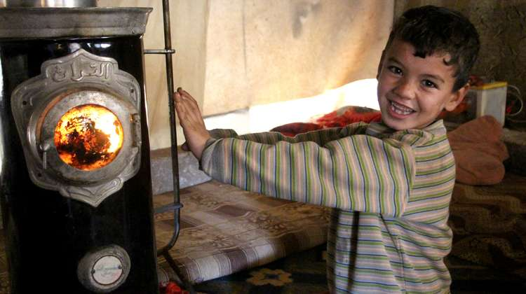 A boy stretches his hands towards a stove whilst smiling at the camera
