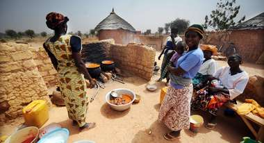 Women boil freshly harvested fruit and vegetables to create healthy food