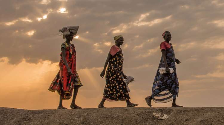 Three women walking at dawn