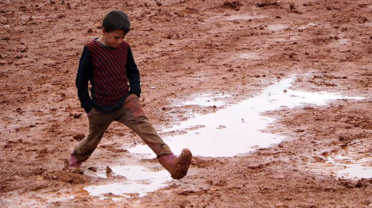 A boy wearing rubber boots walks through mud and puddles